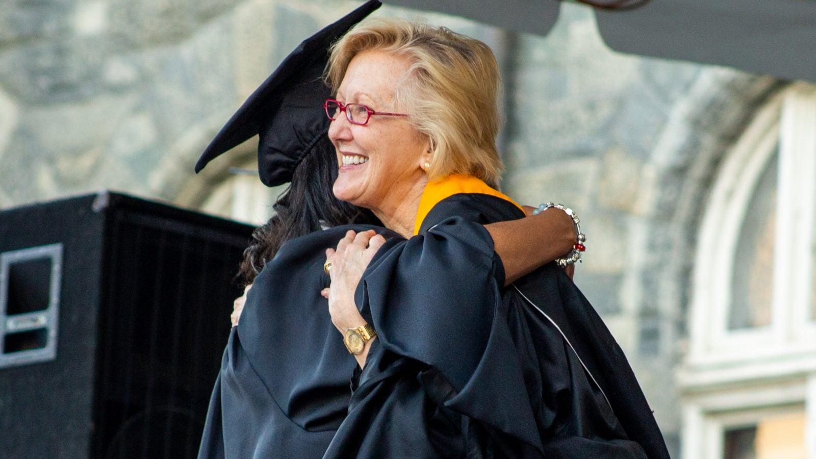 Graduate hugging staff member