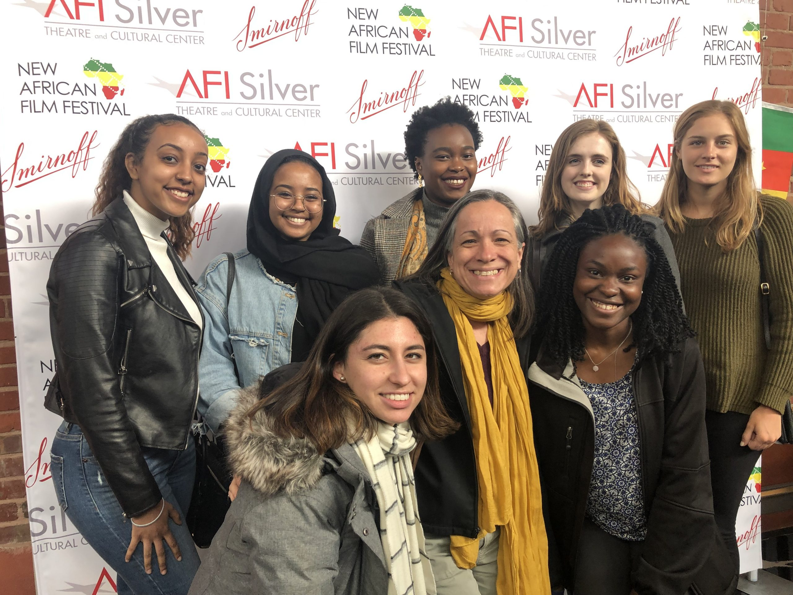 Smith with group of students in front of the photo banner at the 2019 New African Film Festival.