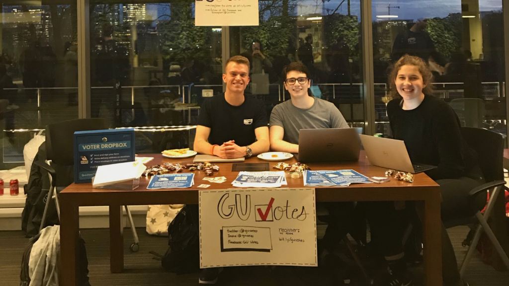 Members of GUVotes sit behind a table with laptops. In front of the table, a sign advertises that they will help students register to vote.
