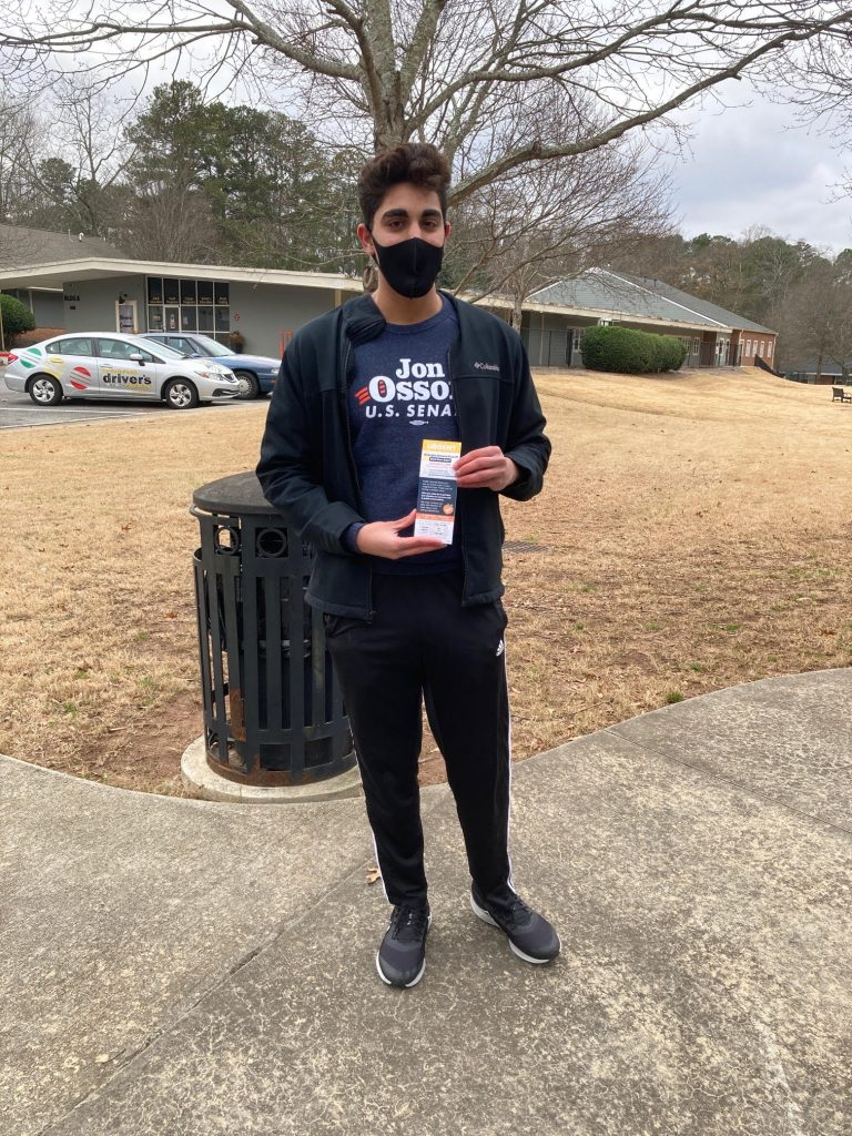 Arash Abbas stands in front of a parking lot. He is wearing a face mask, a Jon Ossoff for Senate T-shirt and is holding an Ossoff campaign leaflet.