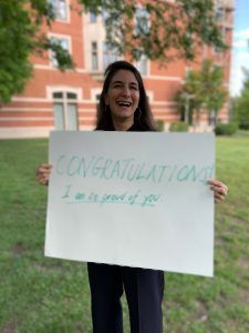 """Prof. Grimm Arsenault pictured on campus with a sign saying """"CONGRATULATION I am so proud of you."""""""