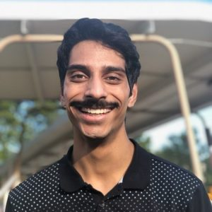 Profile photo of Shuait Nair. He is smiling and wearing a black collared shirt.