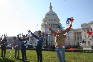 Garcia Escobar Plascencia and other college-aged advocates hold up a paper chain of butterflies in front of the U.S. Capitol Building at a 2017 protest calling for the continued protection of DACA recipients.