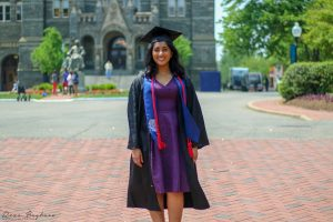 Mittal wears a purple dress and graduation cap and gown. She is standing in Georgetown's front circle in front of Healy Hall.
