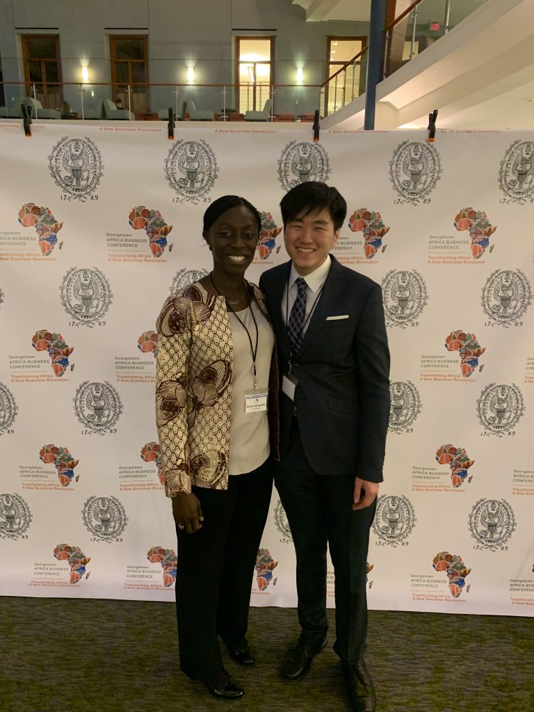 Kim and Sylvia Amegashie (MSFS'19) stand together wearing business attire and conference lanyards. Their background displays the Georgetown University logo and the logo of the Georgetown Africa Business Conference