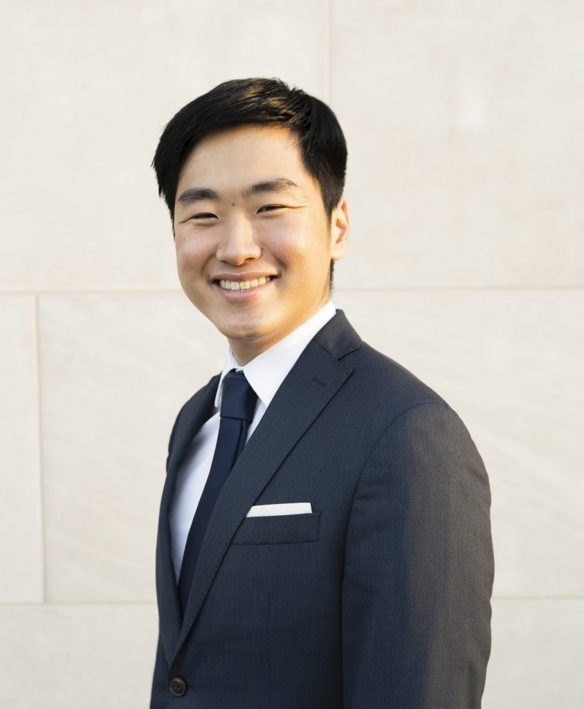 Headshot of Isaac Kim. He is pictured in front of a white wall wearing a dark grey suit, with a dark-colored tie and a white pocket square.