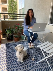 Dale-Huang sits at a small table on the porch of her apartment, working on her laptop. Next to her is a small white dog named Sprout.
