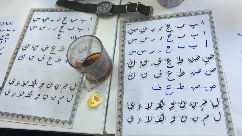 Arabic calligraphy exercises lie on a table next to a cup of tea and a watch.