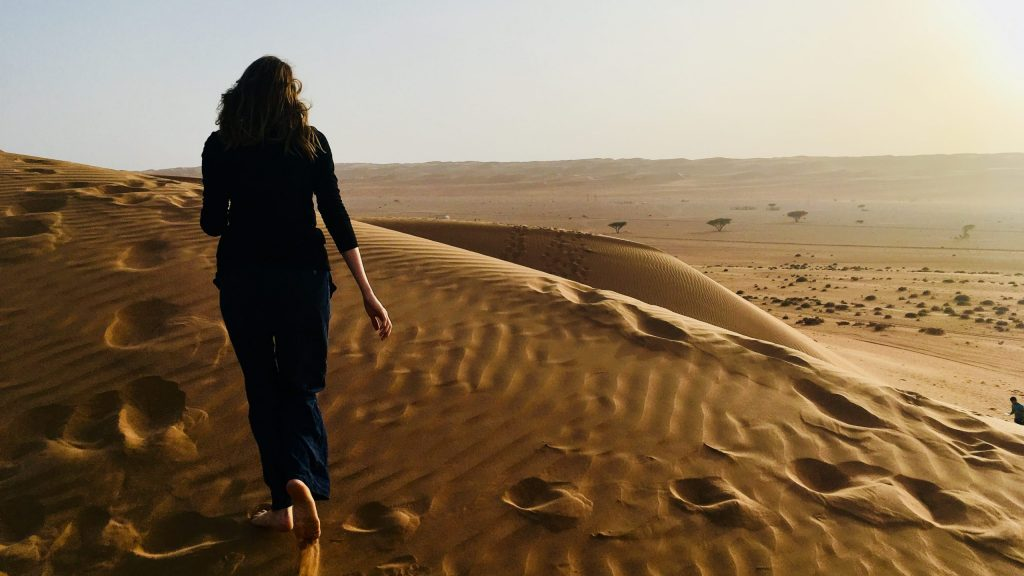 Caris is pictured walking across a sand dune, leaving footprints in the sand.