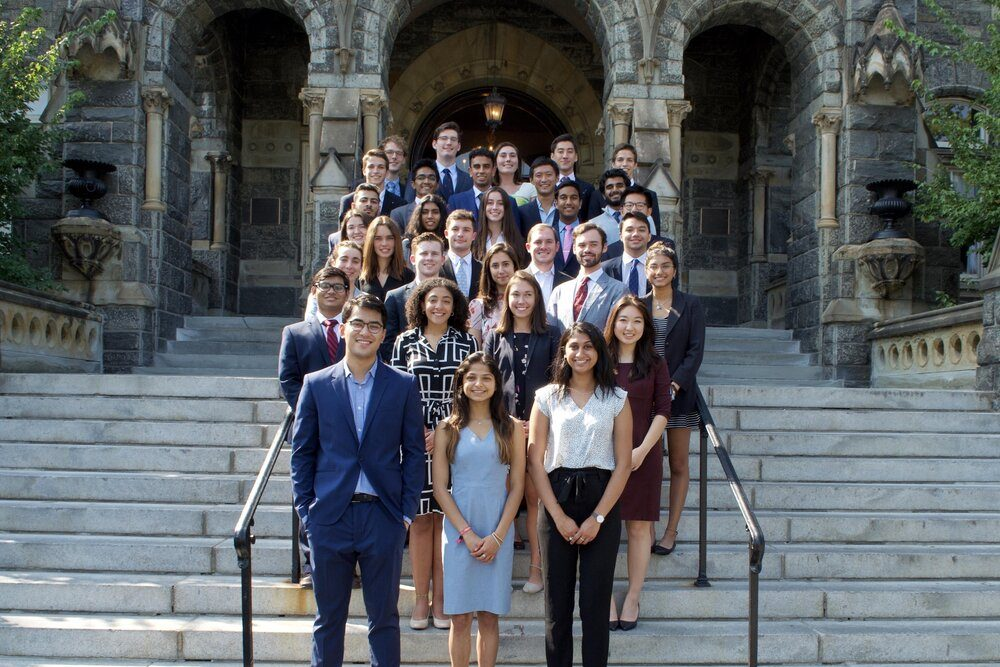 Daly and the Georgetown Global Consulting group's Fall 2020 members pose in front of Healy Hall. All are wearing business professional attire