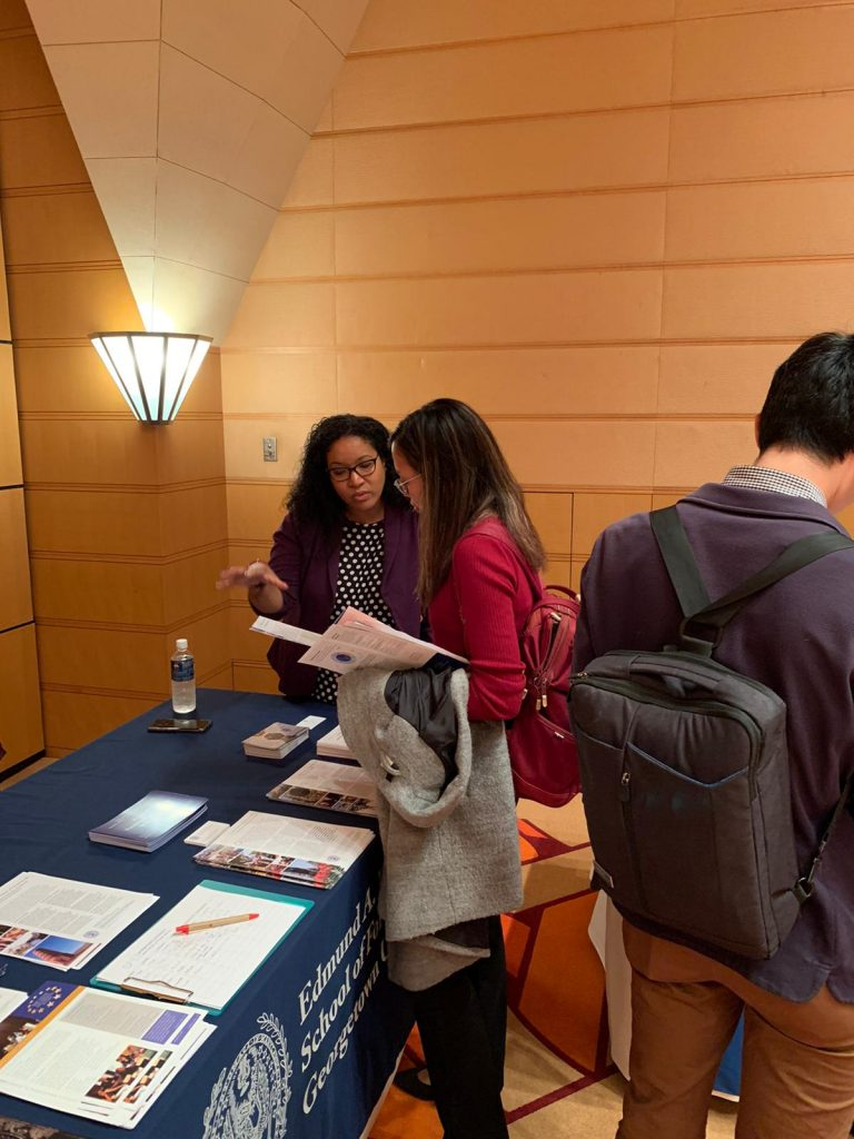 Ja'net DeFlorimonte pictured standing next to a table with promotional material. She is talking to a prospective student who is holding a brochure.