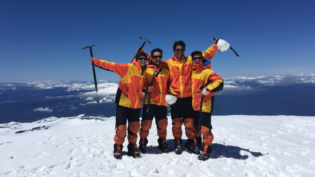 Britt and three friends are pictured on a snowy mountaintop. They carry ice axes.