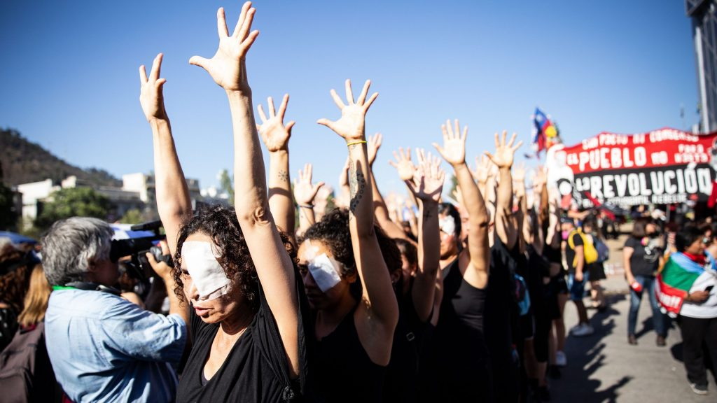 A group of women are lined up with their hands up. A bandage is taped over each of their left eyes.