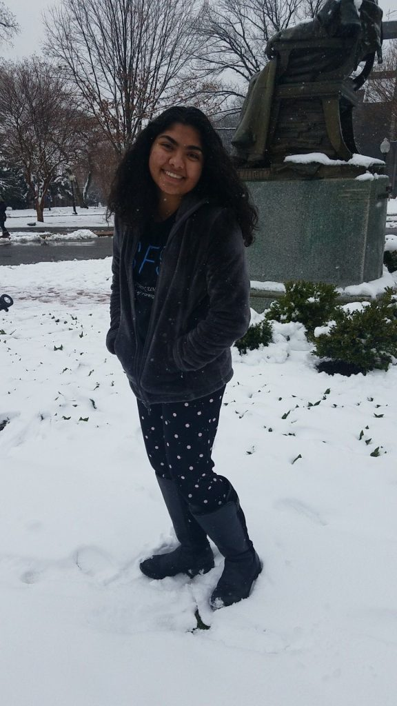 Varsha Menon (SFS'21, MSFS'22) stands smiling in the snow in front of the statue of John Carroll in Georgetown University's front circle