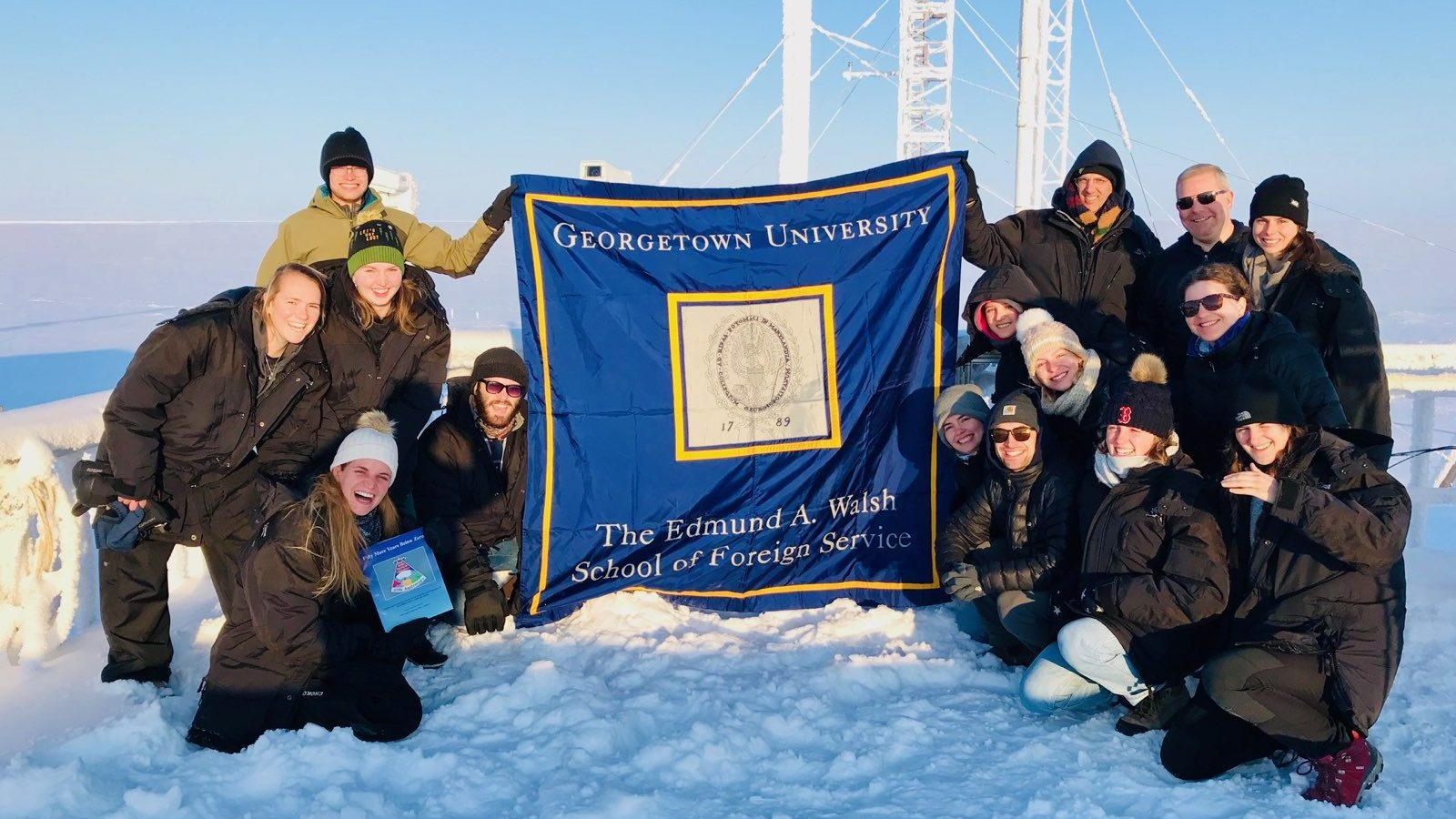 SFS students and professors pose in the snow. A mast is visible behind the group, which carries an SFS banner.