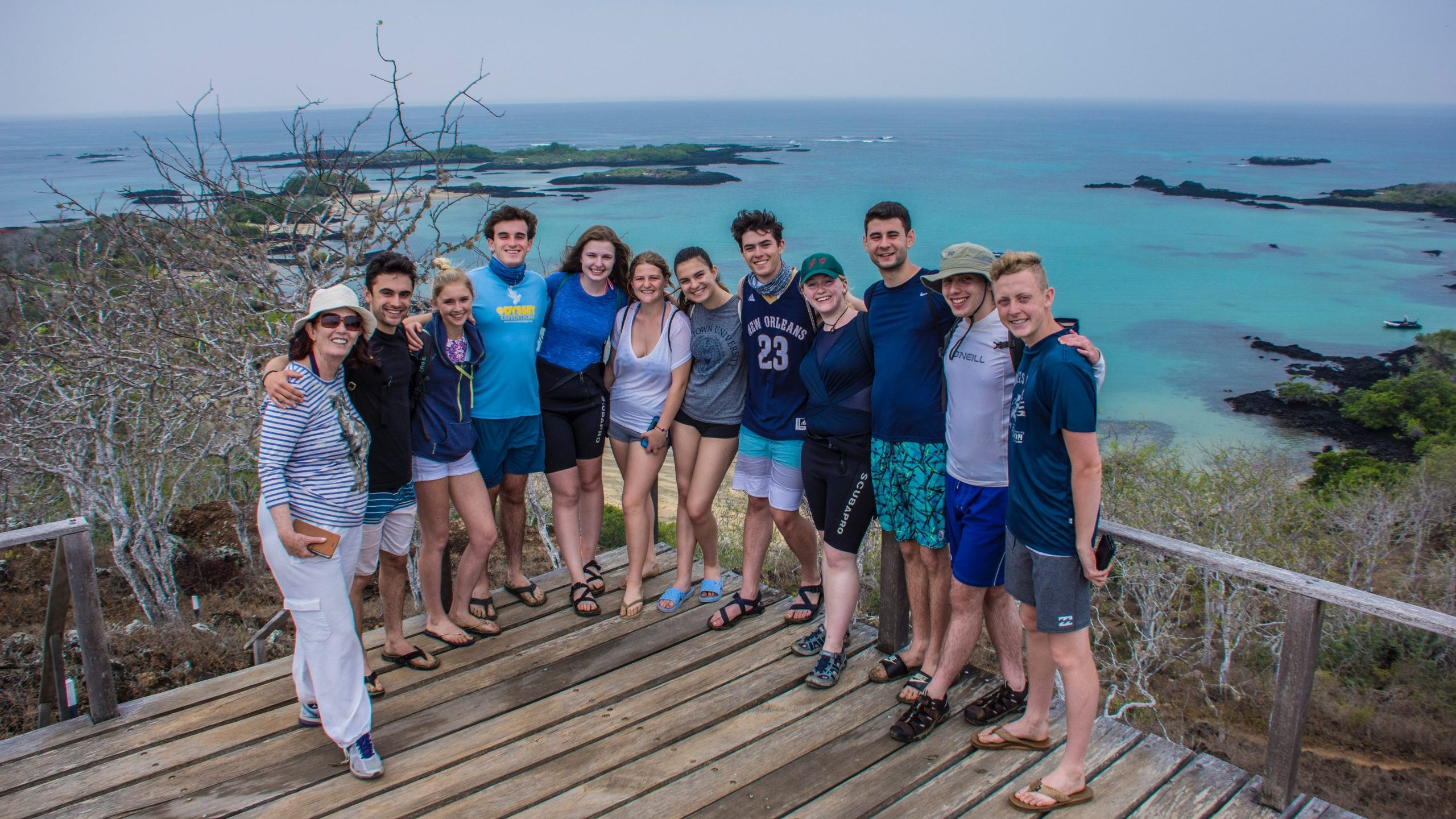 Britt is pictured with a group of fellow students. The are standing on an overlook with the sea in the background.