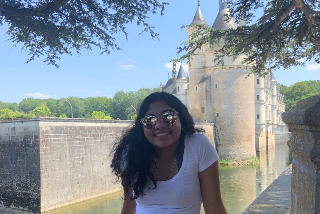 Menon is posing in front of a French castle. She is wearing mirrored sunglasses, a white shirt and a patterned skirt.