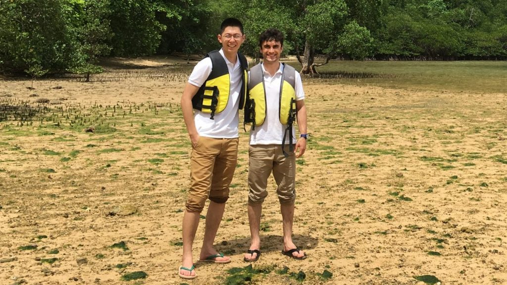 Briant Britt is pictured with a friend. They are on a sandy, grassy beach and wearing life jackets.
