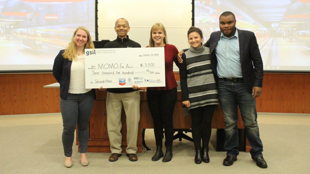 Jimmy is pictured with his Social Innovation Lab teammates holding a large check as they win second prize in the competition.