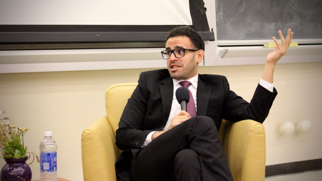 Mohamed Soltan is pictured seated for a panel event. He is wearing a suit and talking into a microphone.