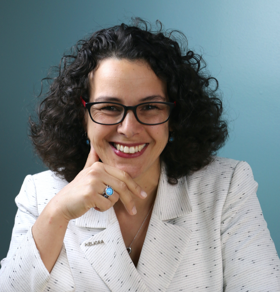 Profile photo of Mrim Boutla against a blue background. She wears glasses and a white blazer. A turquoise ring is visible on her hand, upon which she is resting her head.