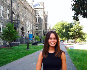 Molly Daly (SFS'21) stands and smiles along the sidewalk in front of Healy Hall on Georgetown's campus.