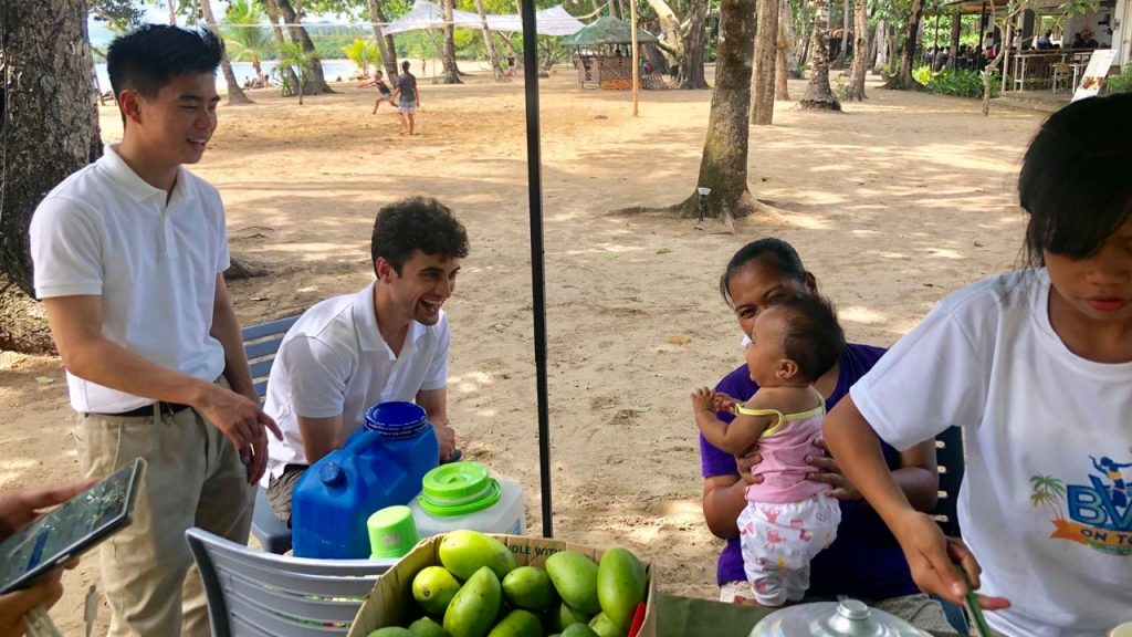 Britt is pictured with another Georgetown students talking to a local mother and her baby in Palawan, the Philippines.