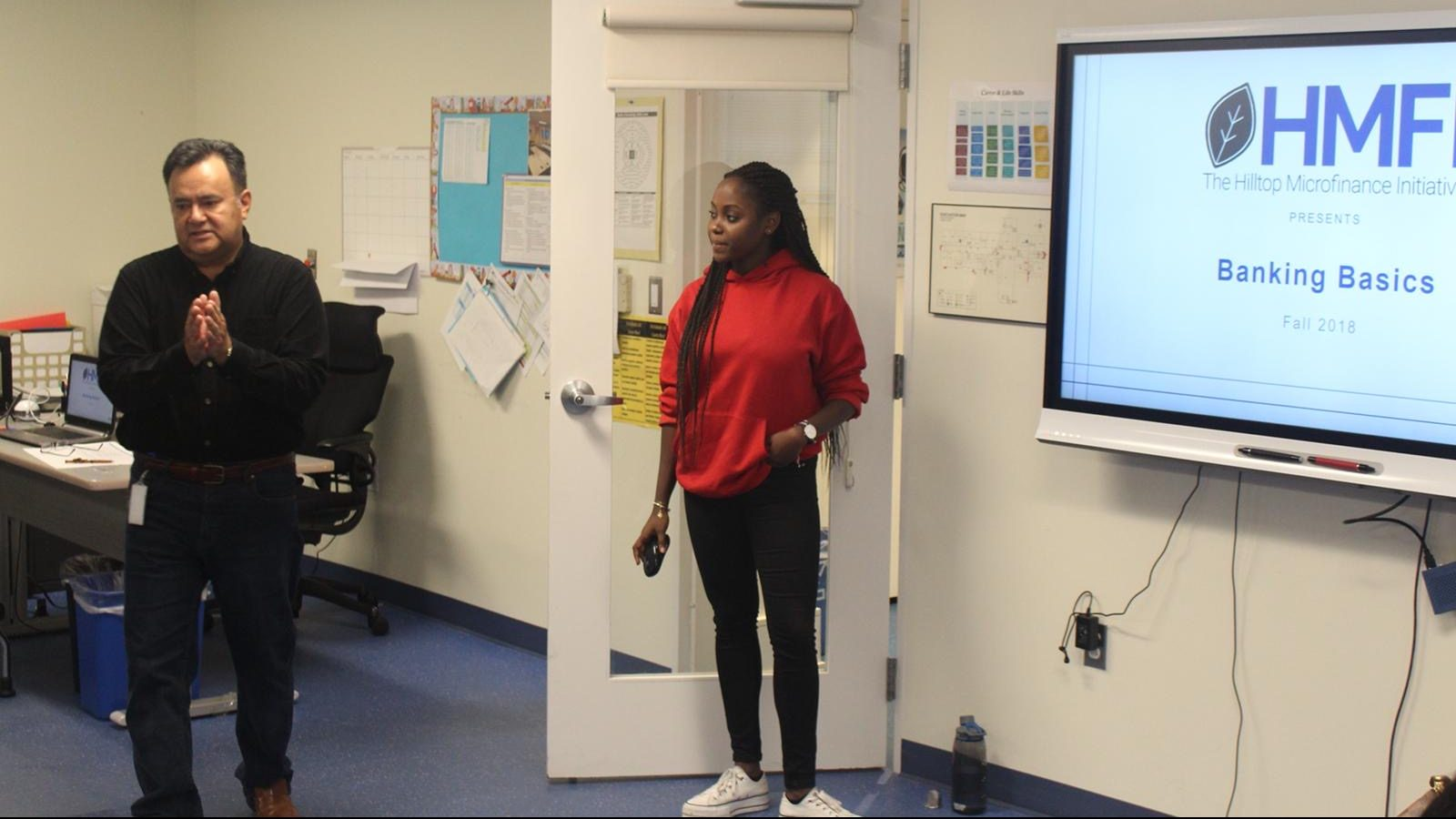 """Travaly is pictured at the front of a classroom next to another instructor. A slideshow with the words """"Banking Basics"""" is depicted on a projector screen behind her."""