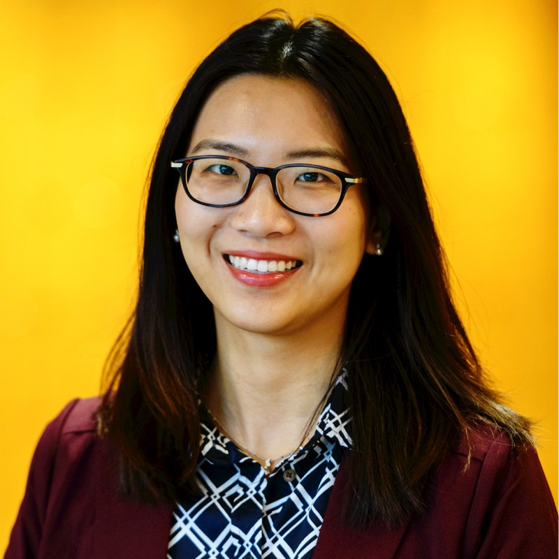 Profile photo of Julie Zhu. She wear glasses, a claret red blazer and a blue and white patterned blouse. The background is solid yellow.