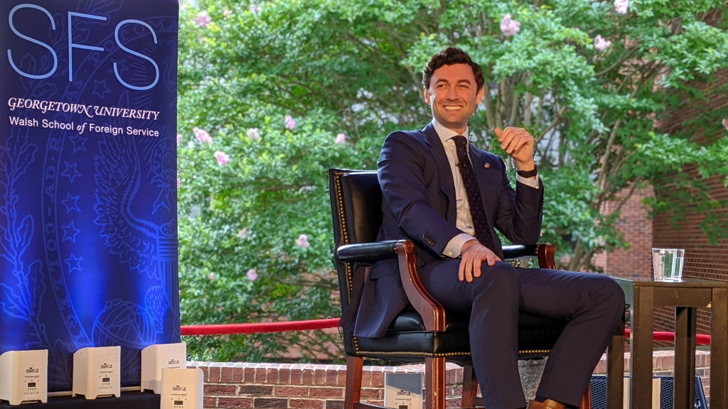Jon Ossoff is seated on a stage in front of an SFS banner. He is looking toward the audience and smiling.