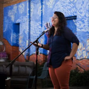 Ishanee Chandha (MSFS'21) stands smiling in front of a microphone in a performance space.
