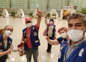 Razick and her colleages, all wearing surgical masks, take a selfie in a mostly empty airport