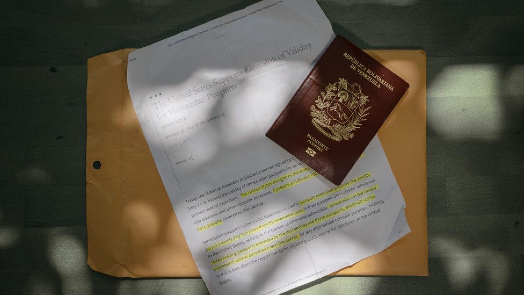 A Venezuelan passport sits atop a pile of immigration documents