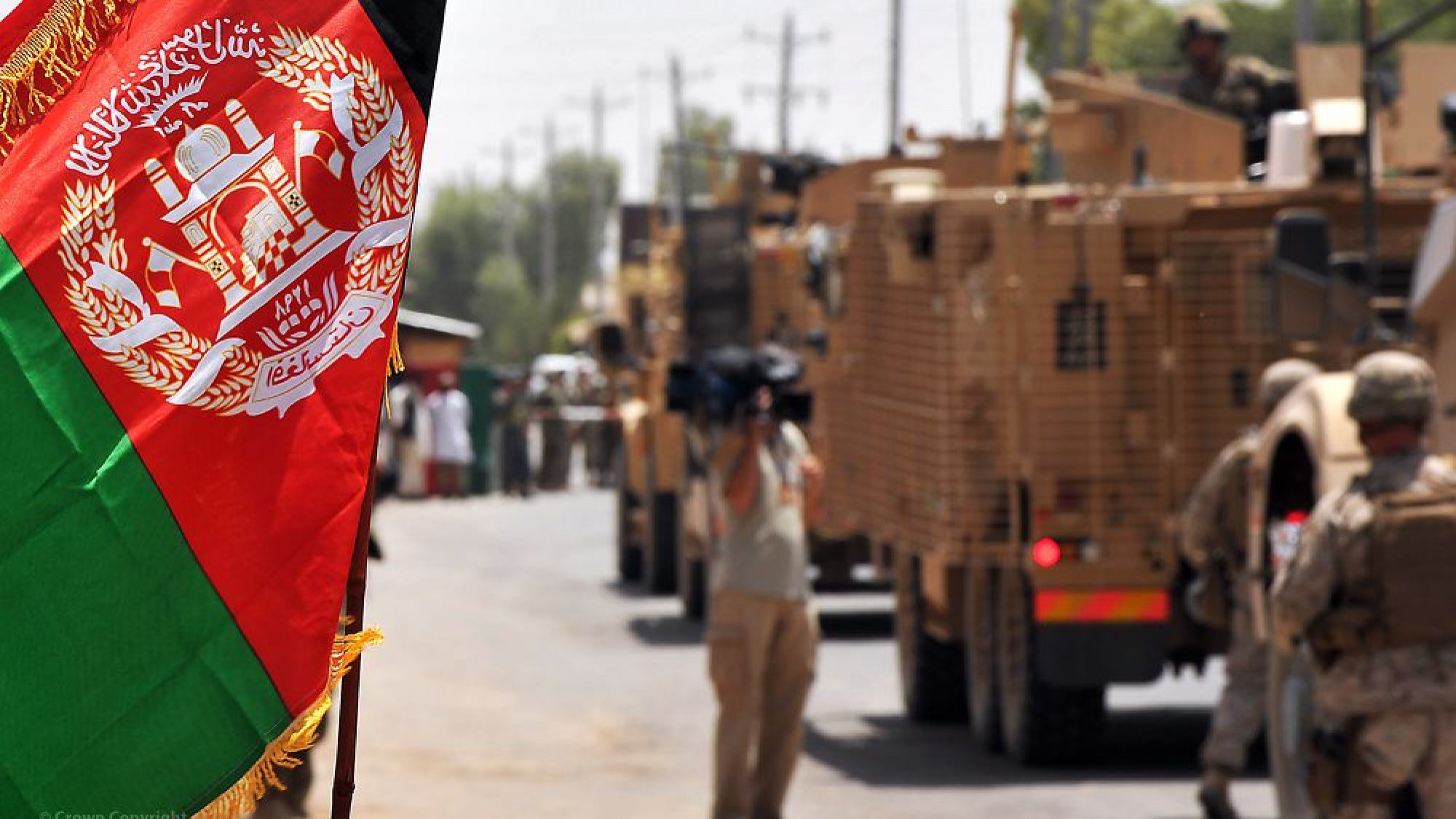 Afghan flag on the foreground, military troops and vehicles are blurred in the backgroud.