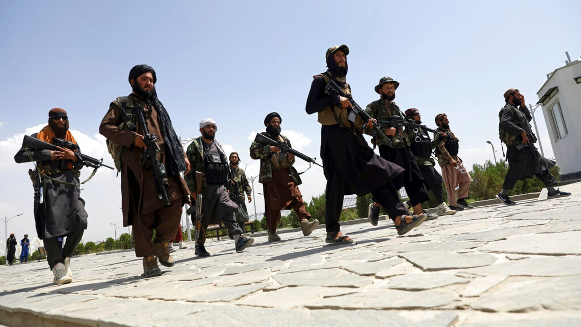 Group of Taliban fighters pictured in combat gear and carrying guns walk the streets of Kabul.