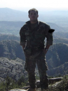Torres, wearing an army combat uniform, standing in front of rolling hills in Afghanistan.