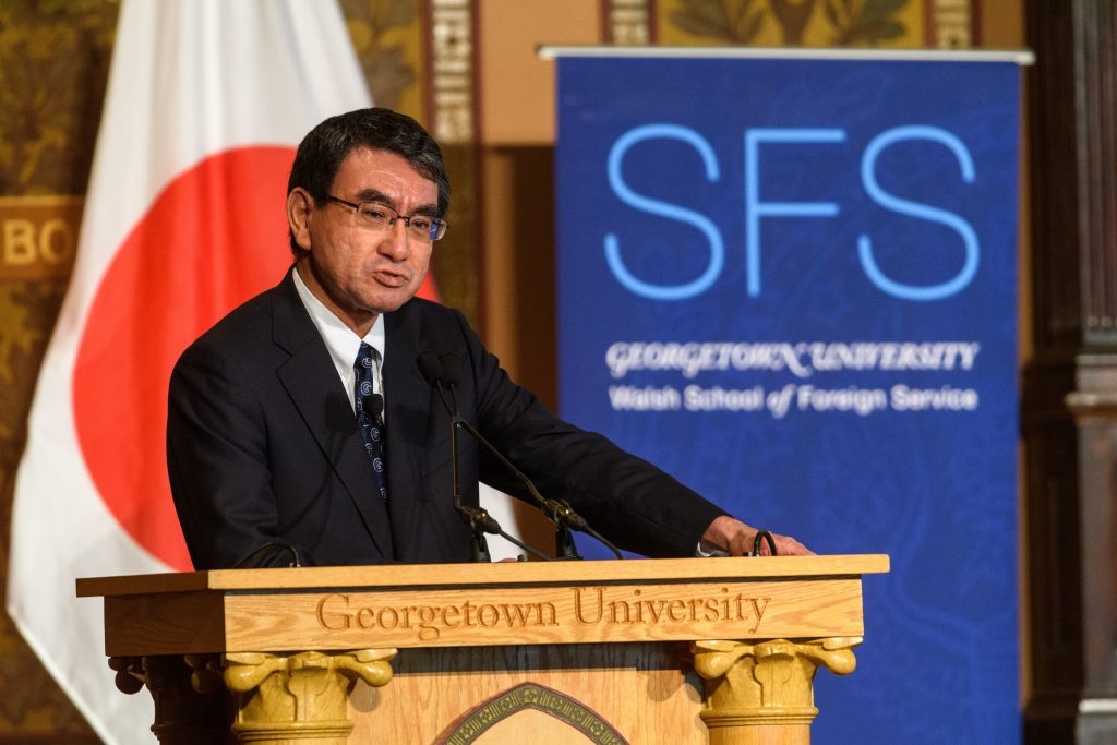 """Kono Taro speaks from podium engraved with words """"Georgetown University."""" An SFS banner and Japanese flag are in the background."""