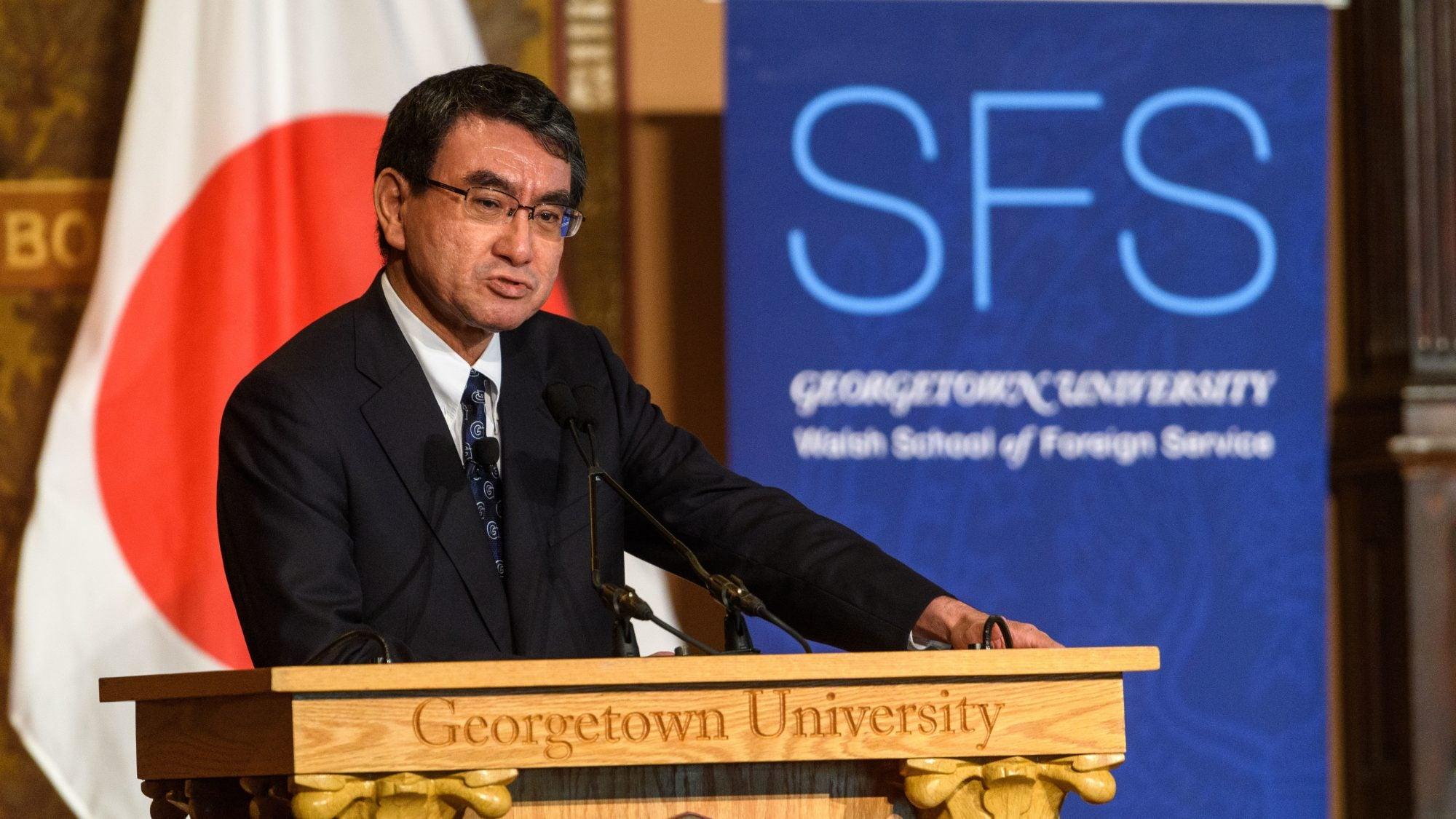Kono Taro speaks from podium engraved with words