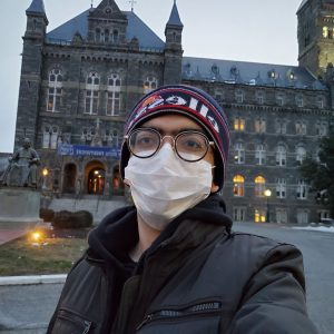 A selfie of Costantin in the early morning in front of Healy Hall. He is wearing a mask and a winter hat.