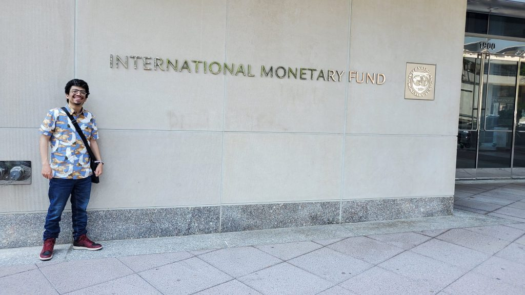 A photo of Costantin posing in front of the International Monetary Fund headquarters in Washington, DC.