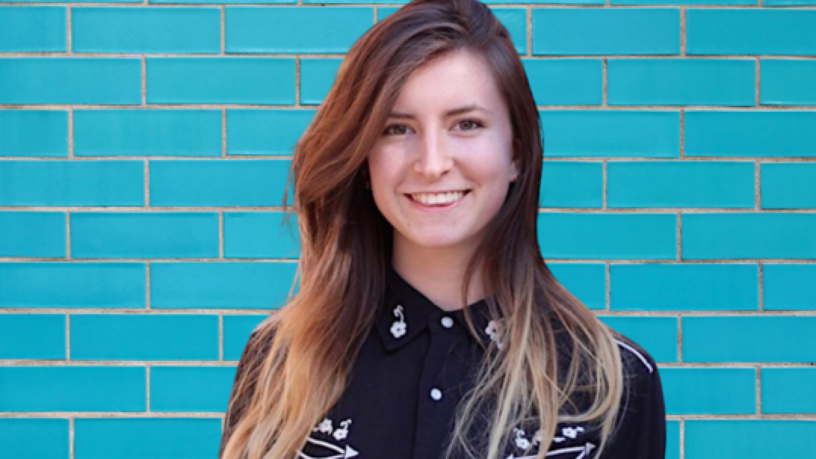 Rebecca Cox poses in front of teal blue brick wall.