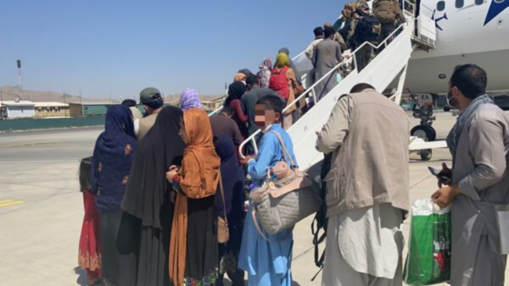 Afghans line up to board a plane. The face of a person facing the camera is pixelated to protect his identity.