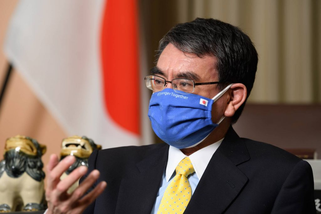 Kono wearing a blue face mask in front of Japanese flag.