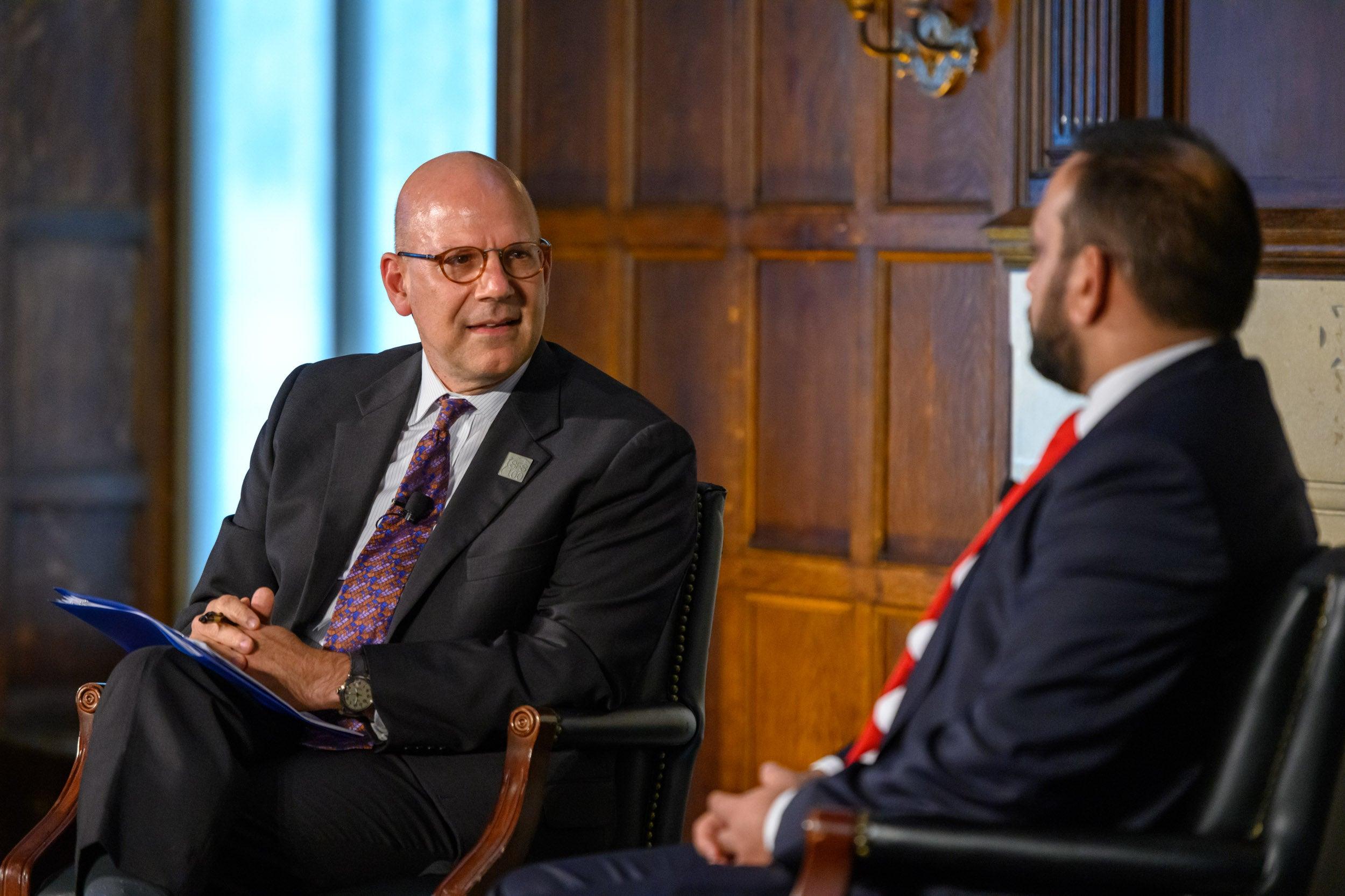 SFS Dean Joel Hellman, wearing a white shirt and purple faces former Afghan Finance Minister Khalid Payenda.