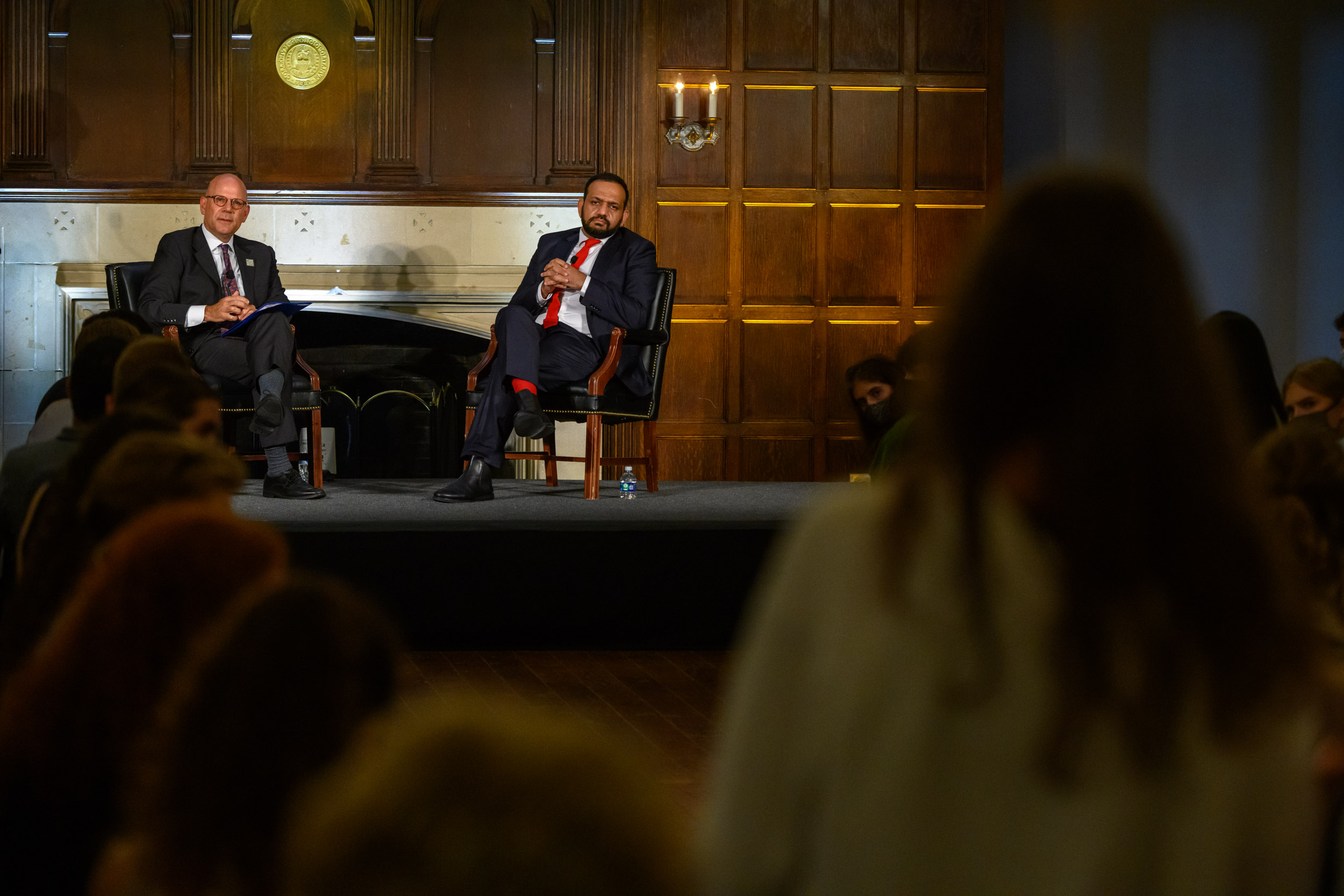 A photo of SFS Dean Joel Hellman and former Afghan Finance Minister Khalid Payenda seated on a stage, taken over the shoulder of a student attendee.