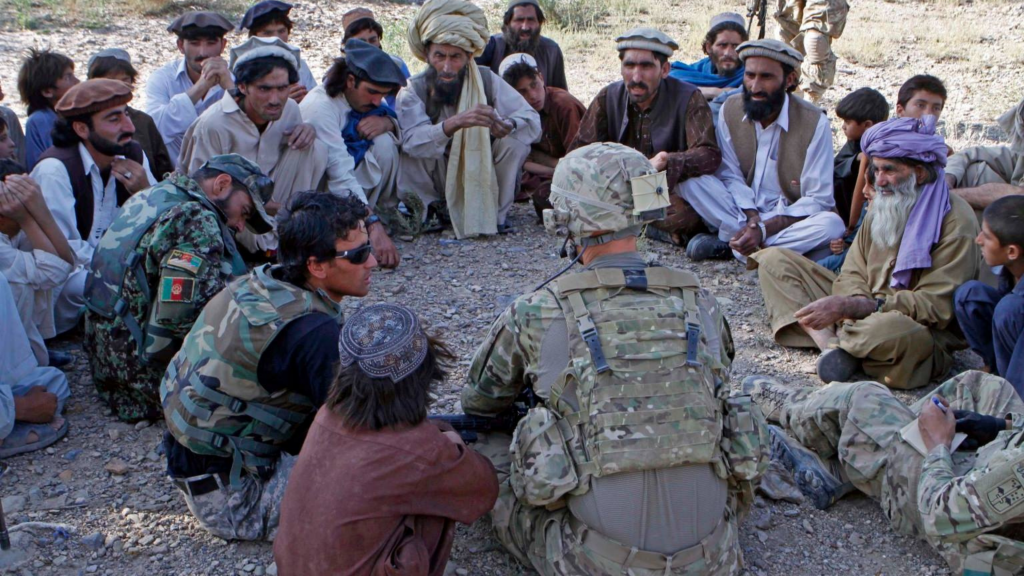A U.S. Army officer talks with a group of Afghan men, sitting in a circle on the ground. An Afghan military interpreter is seated in the group.