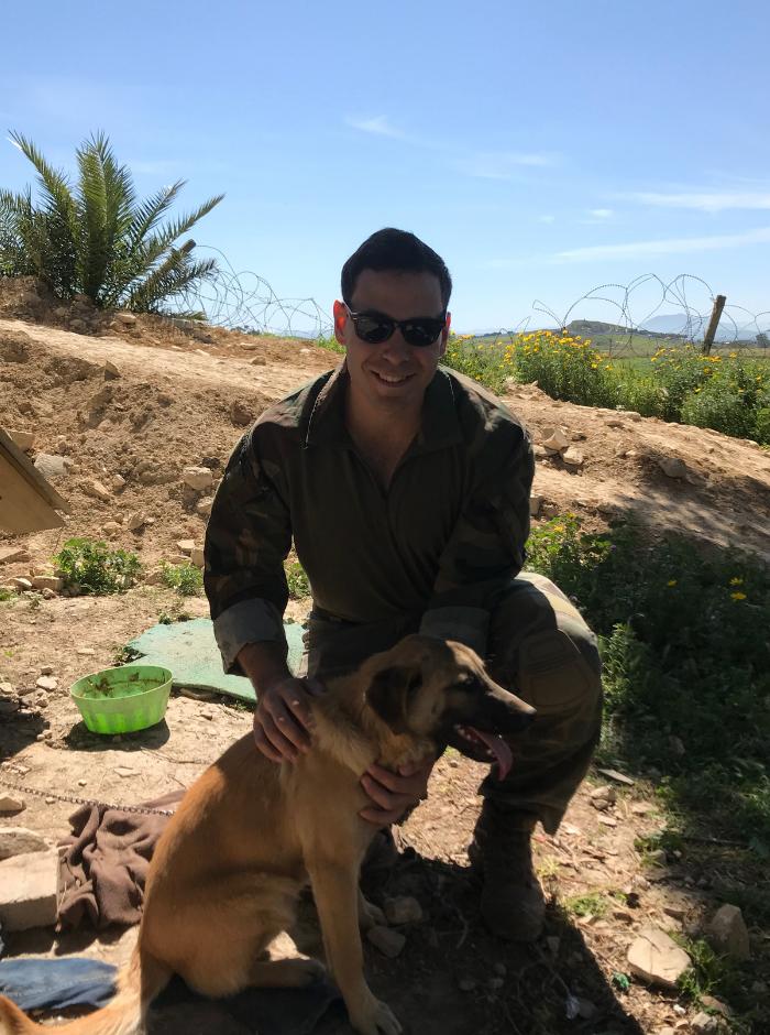 Zach Pyle wears combat gear. He is in a sandy landscape, petting a dog.