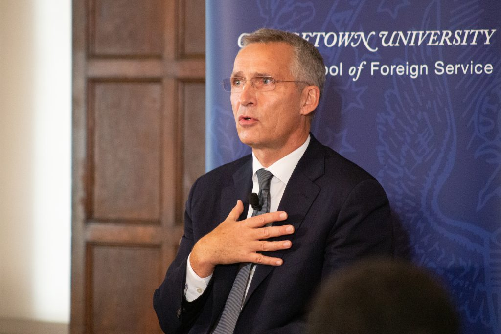 Stoltenberg sits in front of an SFS banner. He is speaking and is wearing a lapel mic.