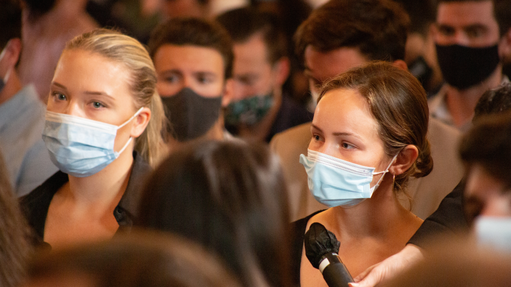 Female student wearing face mask speaks into a microphone.